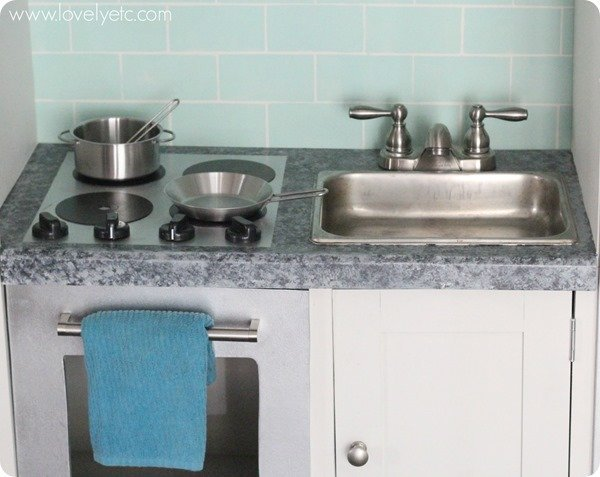 Super realistic play kitchen made really inexpensively using old furniture and paint.