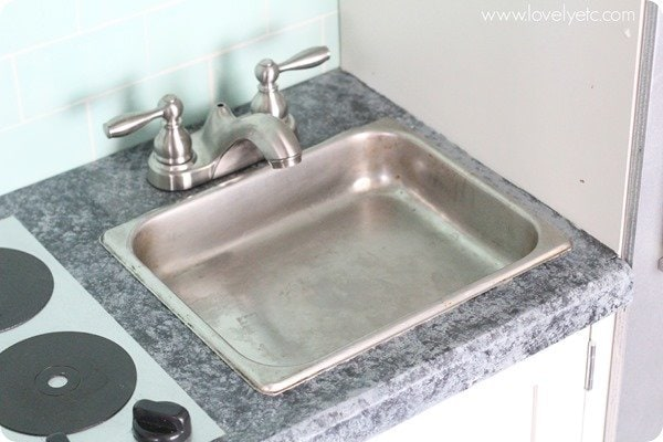 play kitchen sink made from a stainless steel pan and a real faucet