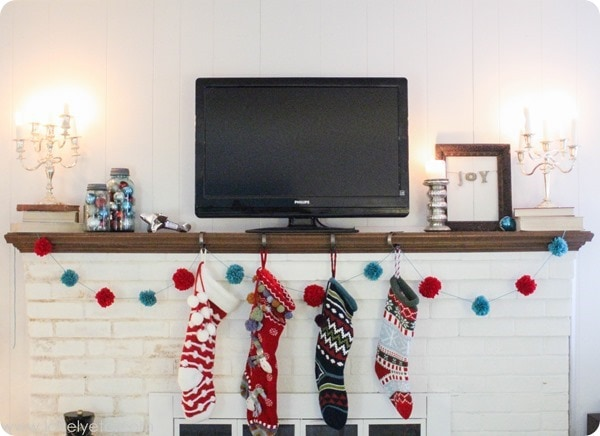 aqua and red christmas mantel with colorful stockings, pom pom garland, and jars of ornaments.