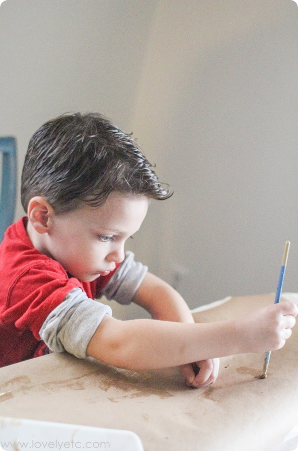 Painting kraft paper with a three year old