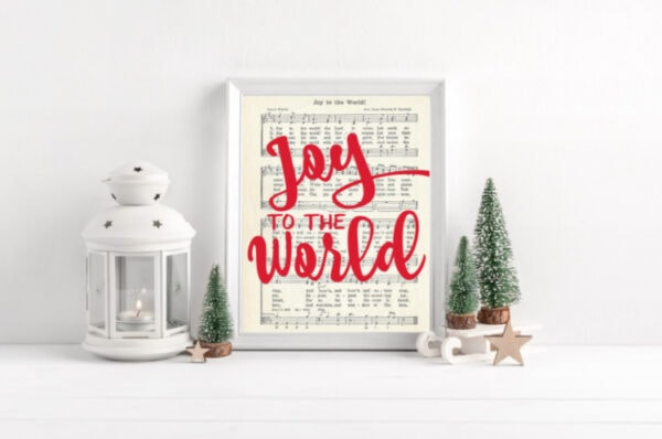 Joy to the world music printable with red script that says Joy to the World, framed next to mini Christmas trees.
