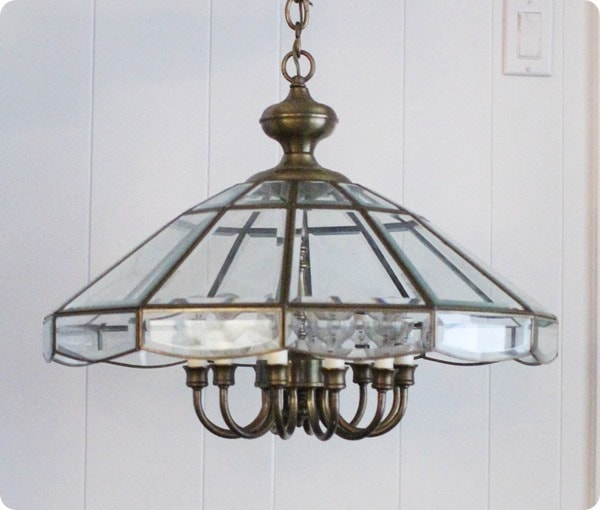 old brass chandelier with a heavy glass shade