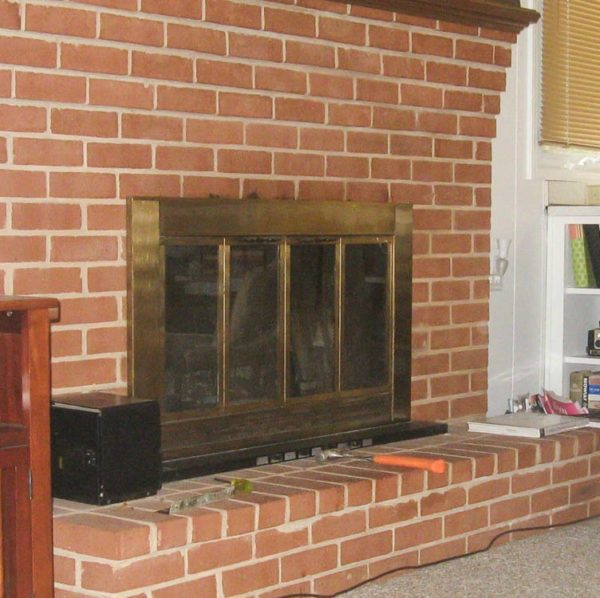brick fireplace with brass fireplace doors before paint
