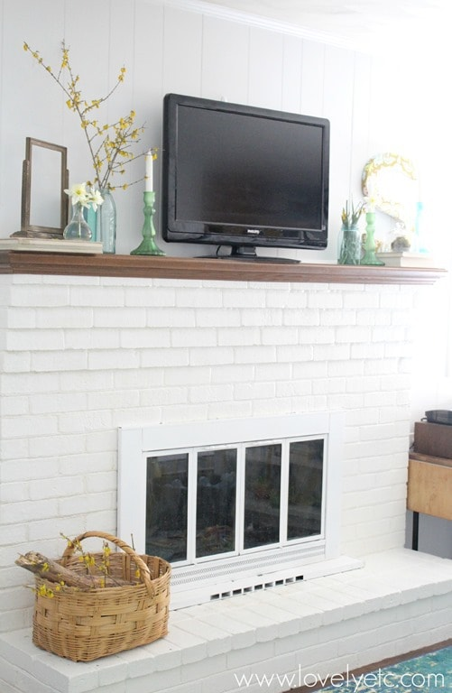 brick fireplace painted white with white fireplace doors