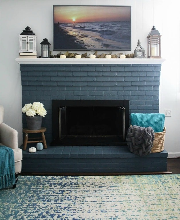 brick fireplace painted blue with small white mantel.