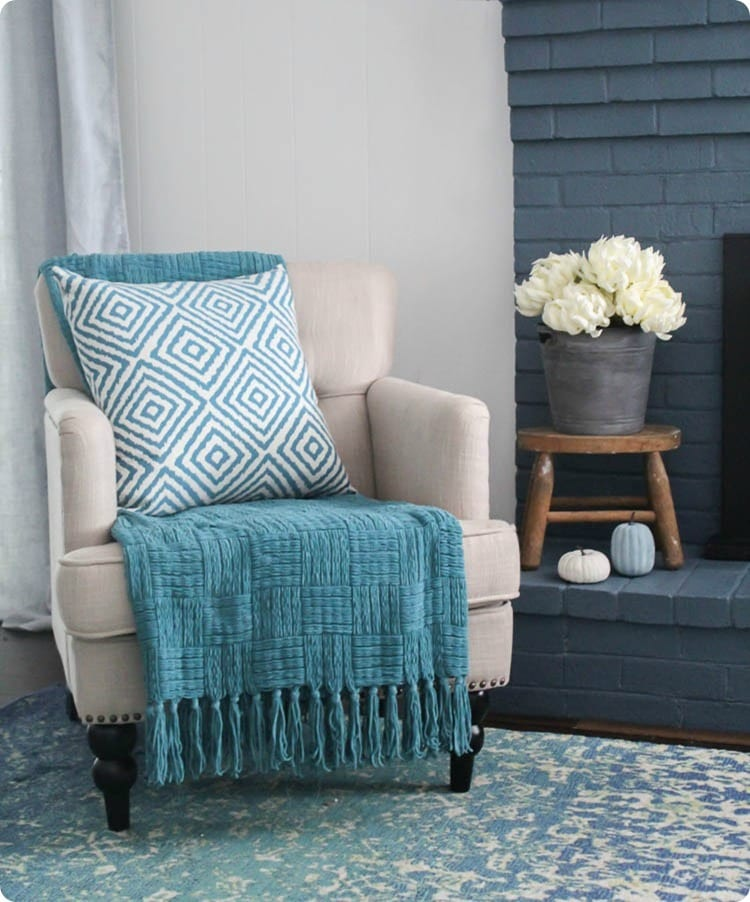 upholstered chair with throw blanket
