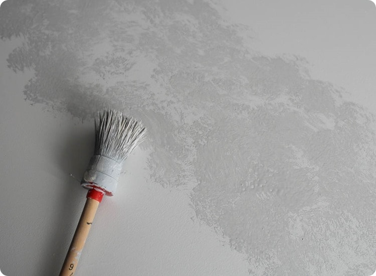 a round paint brush adding gray paint to countertop