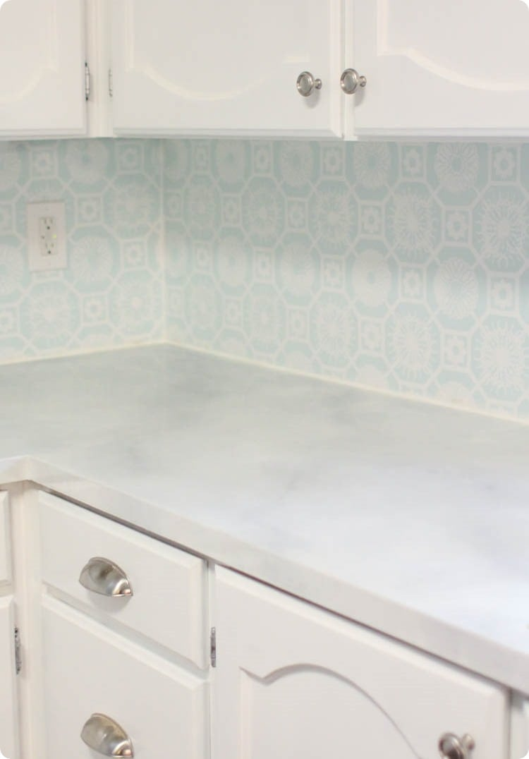 kitchen with laminate countertop painted like marble, painted white cabinets, and a painted backsplash