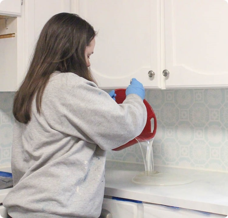 Woman pouring envirotex lite from a bucket onto painted countertops