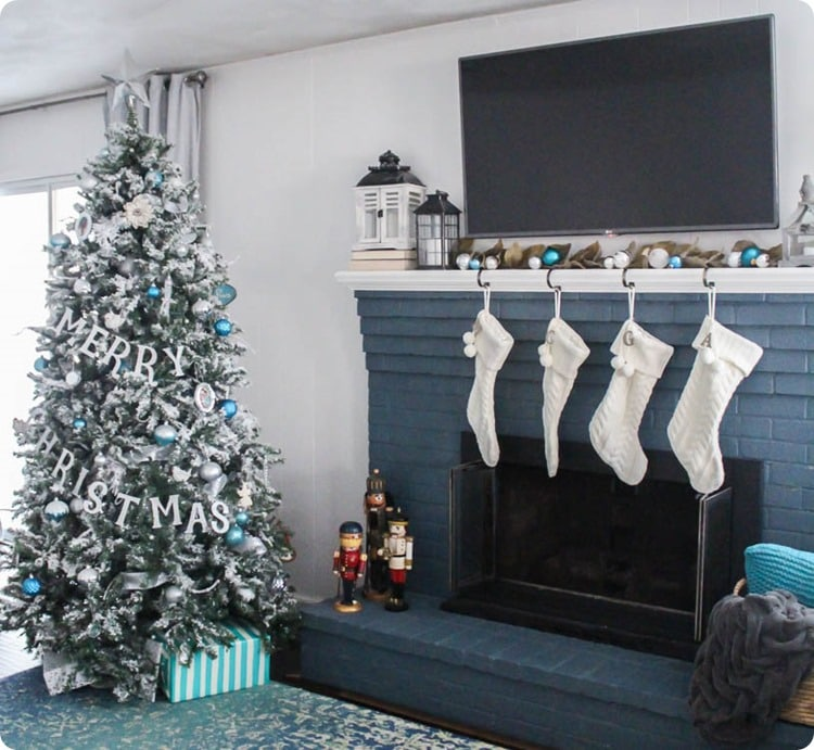 Christmas tree with blue and white ornaments next to dark blue fireplace with white stockings.