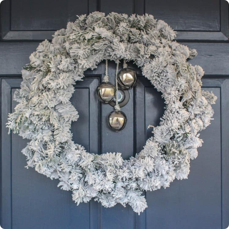 flocked christmas wreath with bells on front door.