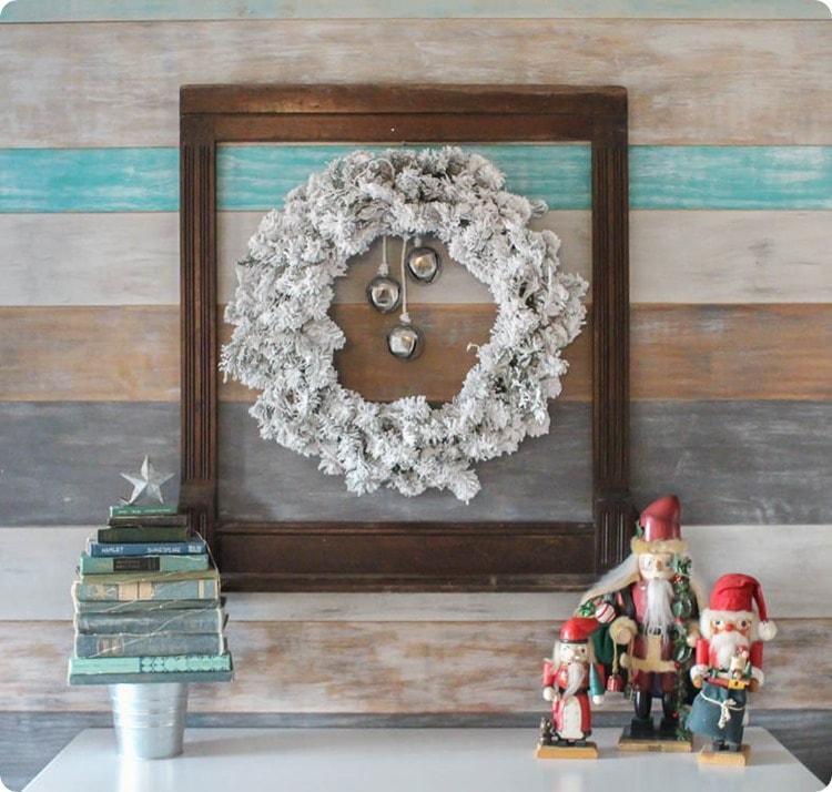 flocked Christmas wreath and vintage frame on wood plank wall.