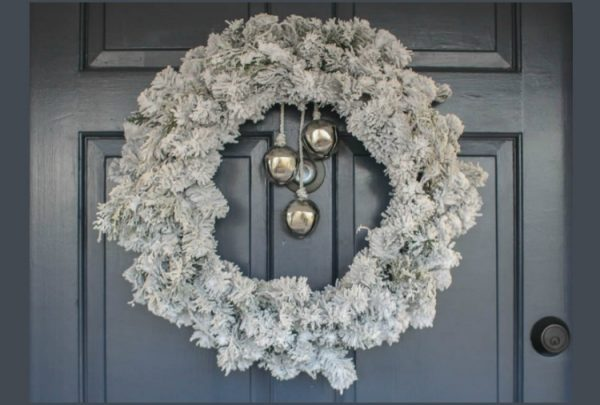 simple evergreen wreath with DIY snow flocking and Christmas bells.