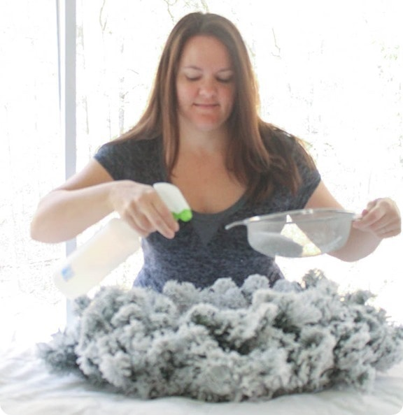 holding a spray bottle and strainer while flocking a basic wreath with snoflock flocking powder