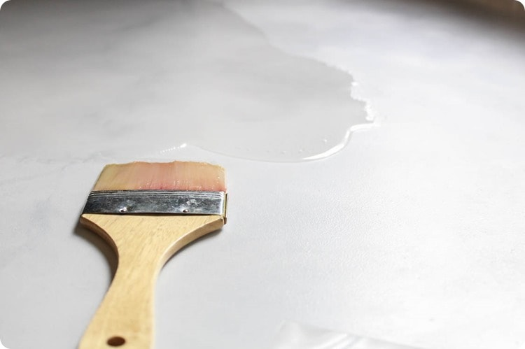 using a paintbrush to spread resin over a painted countertop