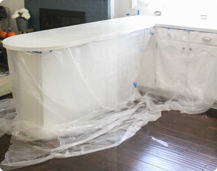 cabinets covered by plastic sheeting in preparation for painting countertops