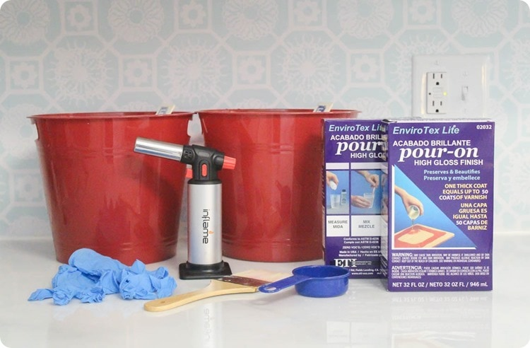 materials for sealing painted countertops - pour-on resin, butane torch, plastic buckets, paintbrush, measuring cup, and gloves