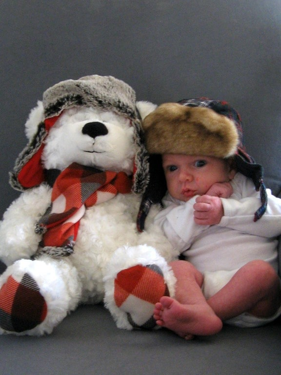 small baby wearing a Christmas hat next to a stuffed bear.