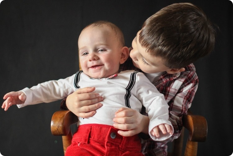 little boy holding baby brother in Christmas photo.