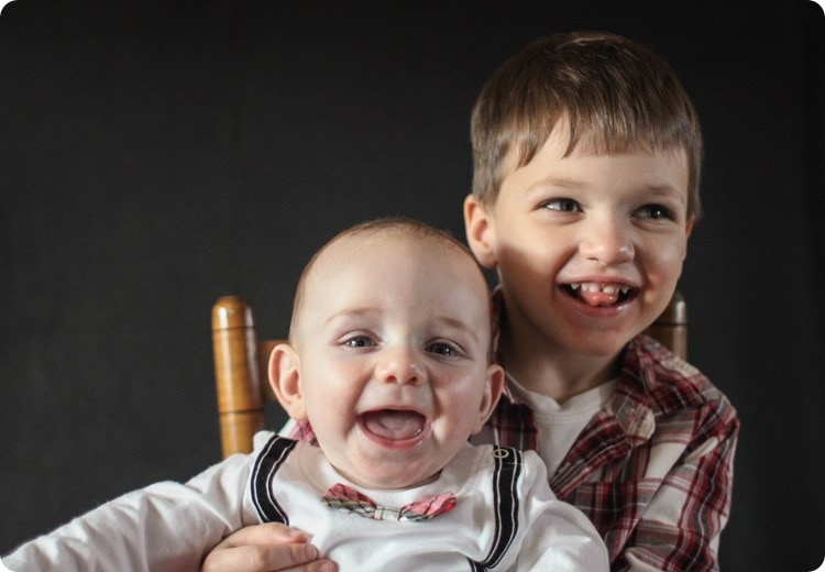 Christmas photo of brothers smiling in a little chair.