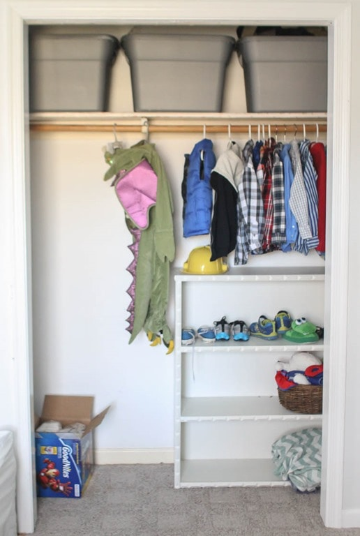 Child's closet before adding diy closet shelves. There is one hanging bar and a bookshelf.