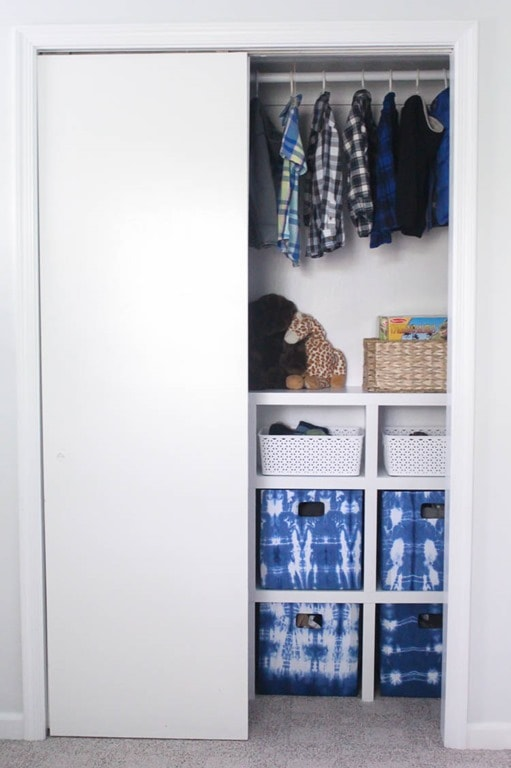 Closet system for small kids closet with sliding doors - with one door open.