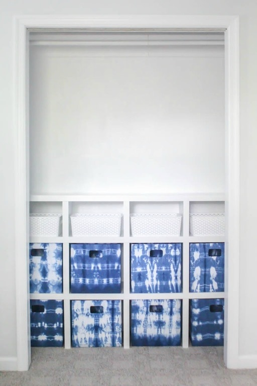 diy closet system with blue and white fabric bins.