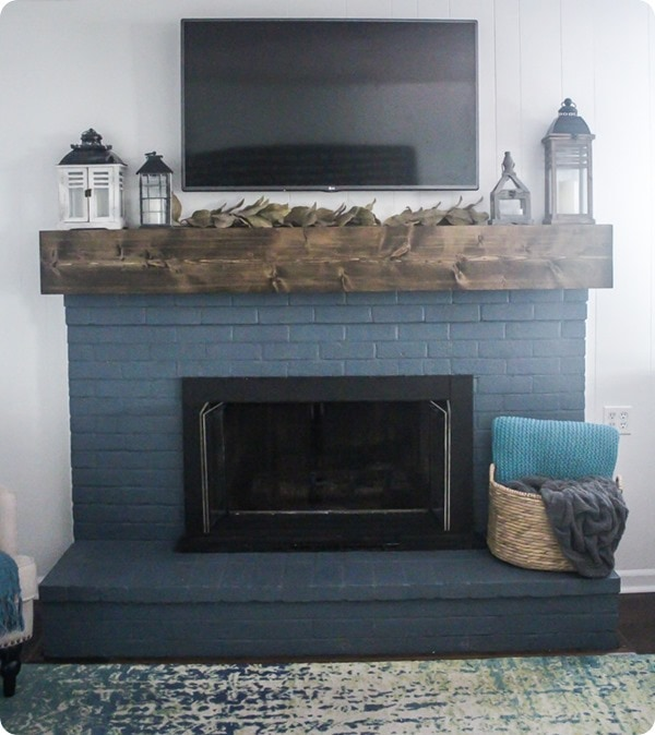 navy fireplace with rustic wood mantel