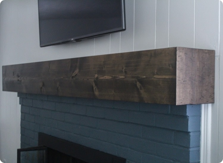 Learn how to build a simple diy fireplace mantel. This rustic mantel has the charm of reclaimed wood but is inexpensive and easy to make.