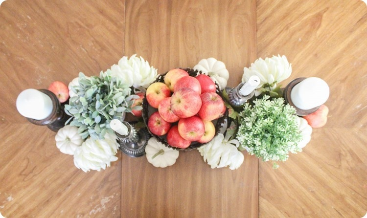fall centerpiece with apples, pumpkins, flowers, and candles