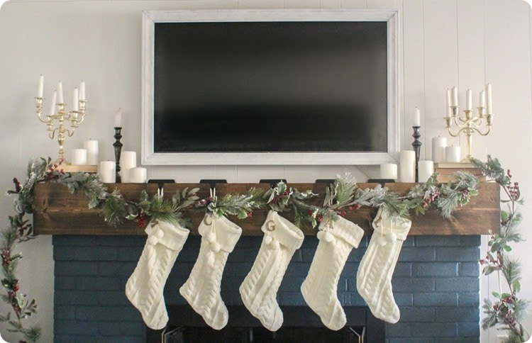 christmas mantel with white stockings and tv