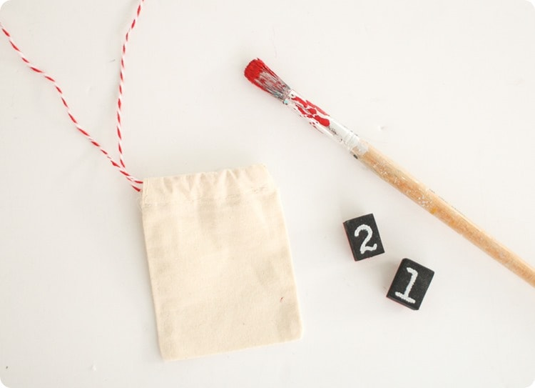 materials to make reusable advent calendar - muslin treat bags, number stamps, and paintbrush with red paint.