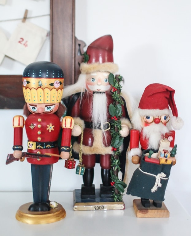 Three wooden nutcrackers - a Christmas soldier and two vintage Santas.