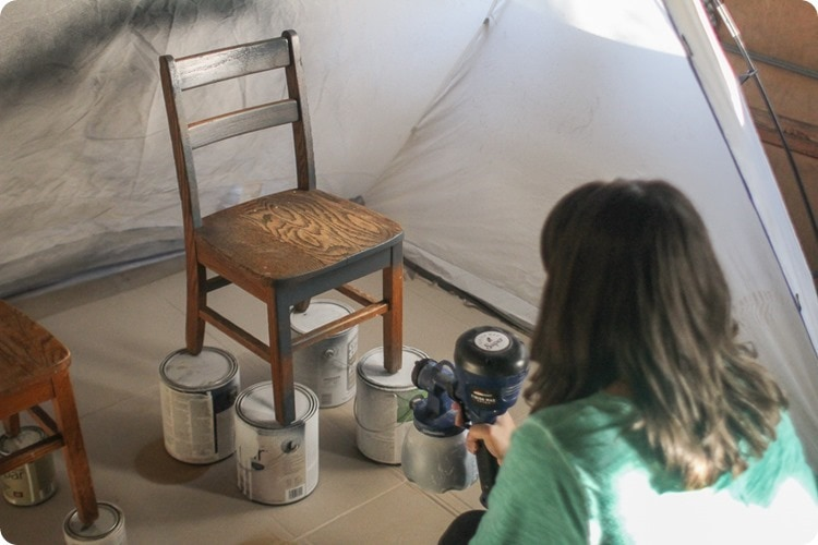using paint sprayer to paint chairs
