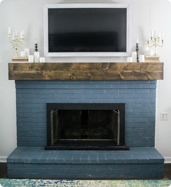 DIY white TV frame shown hanging over blue brick painted fireplace.