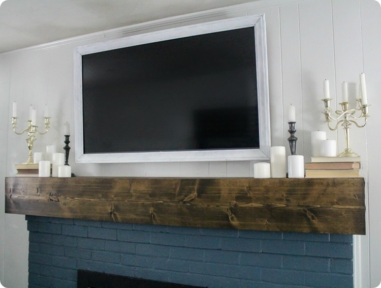 white pained tv frame hanging over brick fireplac.e