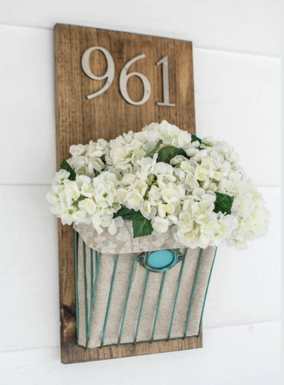 diy house number with a wooden background and a metal basket full of faux flowers