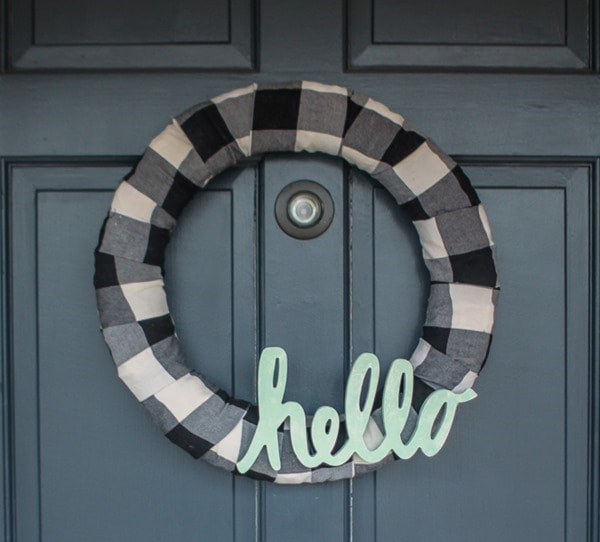Make an easy buffalo plaid modern farmhouse wreath and add a simple hello. It's the perfect way to upcycle a plaid shirt or simply buy a bit of buffalo plaid fabric.