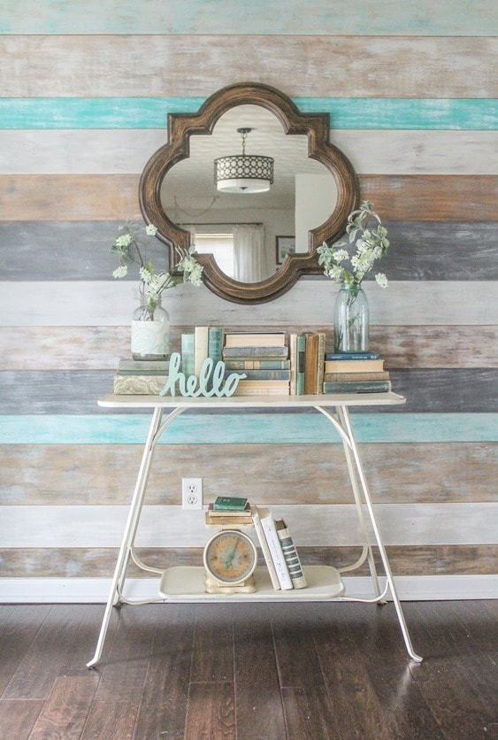 Simple spring entryway decor. Wood wall, quatrefoil mirror, old books, and flowers in mason jars.