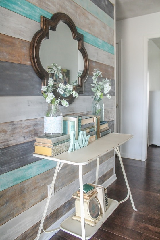 Spring entryway with wood wall, old books, and thrifted treasures.