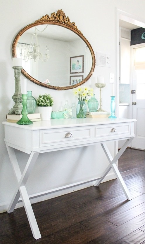 modern white X leg table and ornate gold mirror