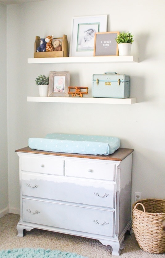 Gray and white dresser changing table with floating shelves in nursery.
