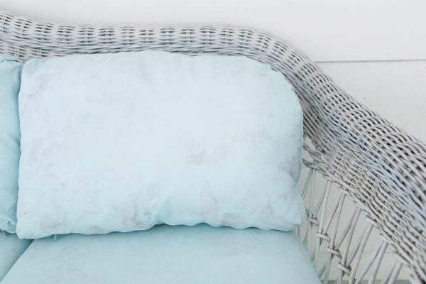 white wicker couch with blue painted cushions