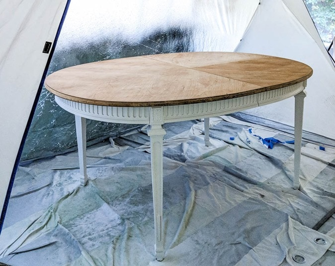 dining table with white painted legs inside spray shelter