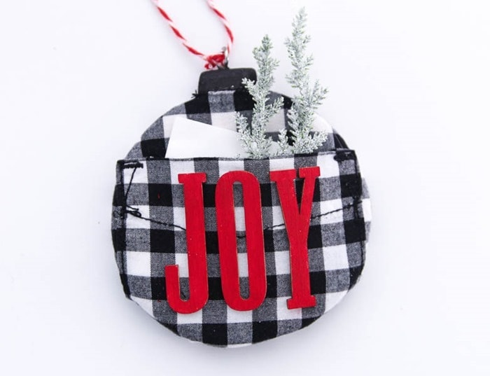 handmade plaid christmas ornament with a note and a few evergreen sprigs tucked in the pocket.