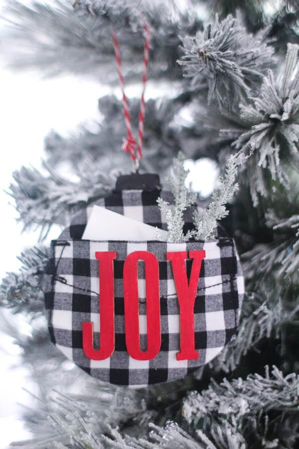 black and white buffalo plaid ornament with red letters that say Joy and a little pocket for holding gift card.