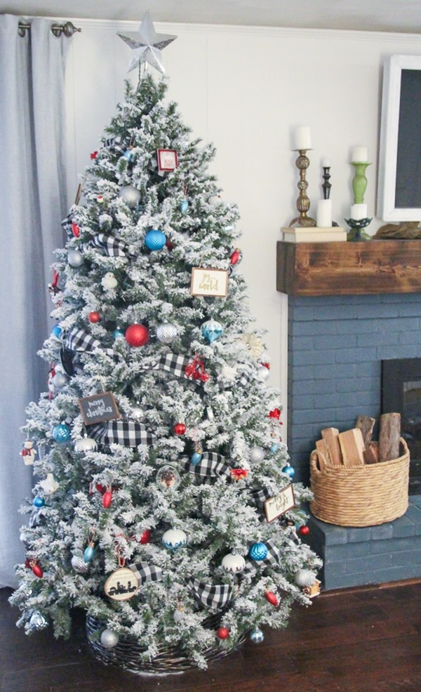 Flocked farmhouse Christmas tree with buffalo plaid ribbon and colorful ornaments.