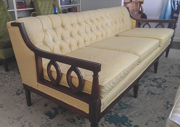 vintage couch with shiny yellow upholstery before reupholstery