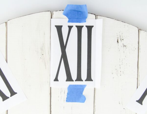 Printout of the clock numbers taped in place on a wooden background.