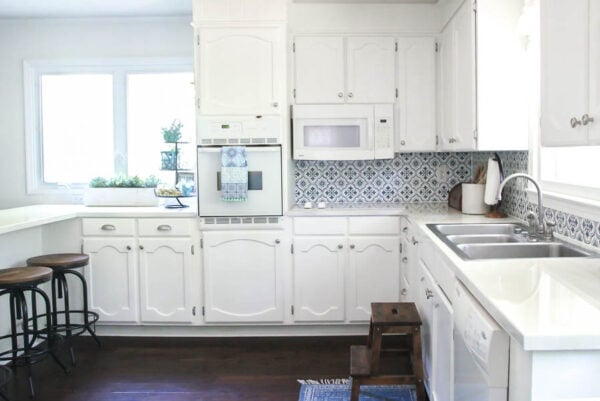 Bright, white kitchen makeover for less than $1000!  With lots of money-saving tips and DIY tutorials for painting cabinets, painting countertops, stenciling a backsplash and more.